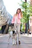 Женщина идя ее собака outdoors и говоря на мобильном телефоне Стоковое фото RF