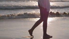 Женщина идя на песчаный пляж около океана Молодая красивая девушка наслаждаясь жизнью и идя на море берег каникула территории лет Стоковое Фото