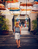 Женщина идя под зонтики в солнечной тропической улице Стоковое Фото