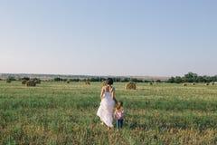 Женщина идя с ее дочерью в поле Стоковые Фотографии RF