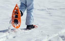 Женщина идя с 2 оранжевыми snowshoes в горах в зиме Стоковое Изображение RF