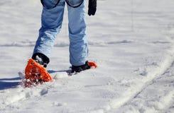Женщина идя с 2 snowshoes в горах в зиме Стоковое фото RF