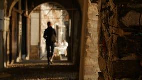 Женщина идя через своды исторических зданий далеко от камеры стоковые фотографии rf