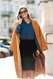 Женщина идя outdoors говорящ телефоном Стоковая Фотография RF