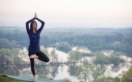 Женщина йоги на зеленой предпосылке парка стоковые фотографии rf