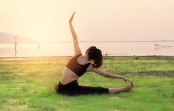 Женщина йоги ослабляет с красивой предпосылкой захода солнца на Стоковые Изображения RF