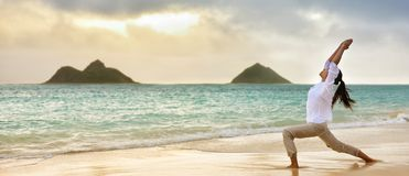 Женщина йоги размышляя в воине я представляю на пляже стоковая фотография