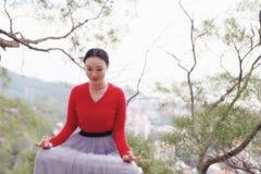 Женщина йоги сидит в представлении раздумья на утесе горного пика стоковое изображение rf