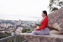 Женщина йоги сидит в представлении раздумья на утесе горного пика стоковое изображение