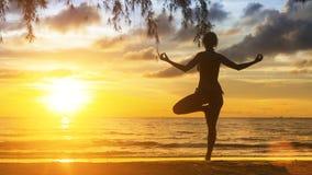Женщина йоги стоя на пляже во время захода солнца стоковые изображения rf