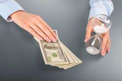 Женщина касается часам и наличным деньгам Стоковая Фотография RF