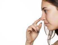 Женщина касаясь ее носу Стоковые Изображения