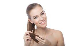 Женщина касаясь концам ее волос, на белой предпосылке Стоковые Изображения