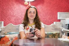 Женщина касаясь на smartphone на ослабляет время в кафе кофе Красивая женщина в кафе использует smartphone Стоковые Фотографии RF