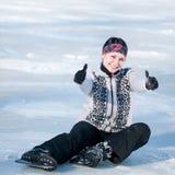 Женщина кататься на коньках льда сидя на льде Стоковое фото RF