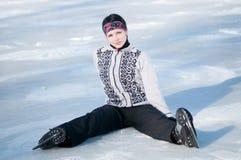 Женщина кататься на коньках льда сидя на льде Стоковые Фотографии RF
