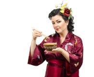 Женщина кимоно есть от шара с палочками Стоковая Фотография