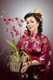 Женщина кимоно кавказская держа орхидею стоковое изображение rf