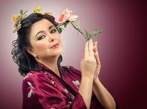 Женщина кимоно кавказская держа розу пинка стоковые фото