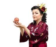Женщина кимоно предлагая красное яблоко стоковая фотография