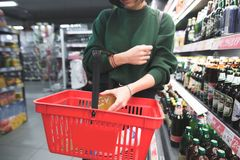 Женщина кладет бутылку спирта в красную магазинную тележкау Девушка кладет приобретение в корзину стоковое фото rf