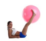 Женщина кладет и принимает шарик пригодности с ногами стоковое изображение rf