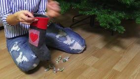 Женщина кладет конфету в носок рождества акции видеоматериалы