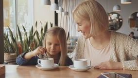 Женщина кладет ложку в чашку ` s дочери на кафе стоковое фото