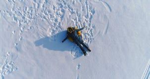 Женщина кладет на трубопровод в снеге Камера медленно поднимая Воздушный отснятый видеоматериал сток-видео