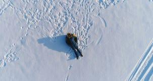Женщина кладет на трубопровод в снеге Камера медленно поднимая Воздушный отснятый видеоматериал видеоматериал