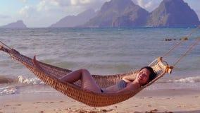 Женщина кладя в гамак на тропический пляж акции видеоматериалы
