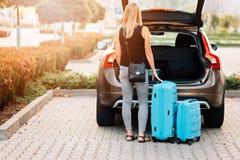 Женщина кладя 2 голубых пластиковых чемодана к багажнику автомобиля стоковая фотография rf