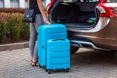 Женщина кладя 2 голубых пластиковых чемодана к багажнику автомобиля стоковое фото rf
