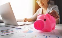 Женщина кладя монетки в розовую копилку стоковое фото