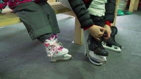 Женщина кладя на коньки льда около маленькой девочки сток-видео