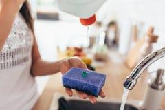 Женщина кладя cleanser к губке для того чтобы помыть лоток в кухонной раковине Блюда руки моя Конец-вверх стоковое фото