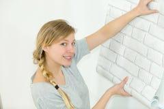 Женщина клеит обои дома стоковое изображение rf