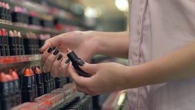 Женщина клиента выбирает новые lipgloss для профессионального макияжа и прикладывает косметики испытывая в наличии в магазине видеоматериал