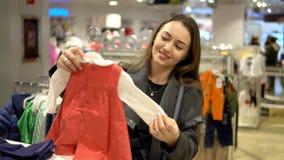 Женщина клиента выбирая одежды младенца в магазине видеоматериал