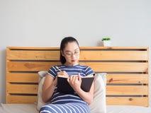 Женщина книга чтения на кровати стоковая фотография rf