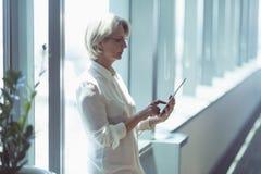 Женщина коммерсантки используя планшет окном Стоковое фото RF