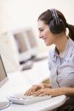 женщина комнаты наушников компьютера печатая на машинке нося Стоковое Изображение