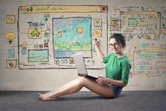 Женщина конструируя вебсайт стоковое фото