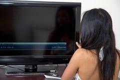 Женщина контролирует телевидение Стоковые Изображения RF