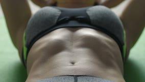 Женщина конца-вверх делая хрусты на циновке тренировки сток-видео