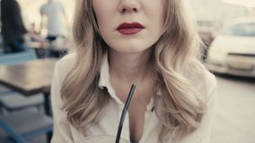 Женщина конца-вверх непознаваемая молодая кавказская белокурая, вьющиеся волосы, с сексуальными красными губами выпивая спиртной  видеоматериал