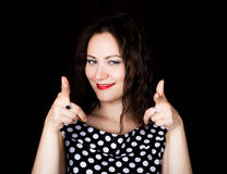 Женщина конца-вверх смотрит прямо в камеру на черной предпосылке показывает различные руки знаков выражает различную Стоковая Фотография
