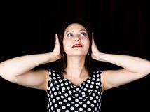 Женщина конца-вверх смотрит прямо в камеру на черной предпосылке смеясь над женщина покрывает его уши с его руками стоковые фото