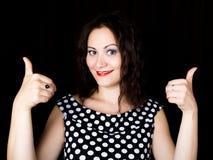 Женщина конца-вверх смотрит прямо в камеру на черной предпосылке показывает различные руки знаков выражает различную Стоковое Фото