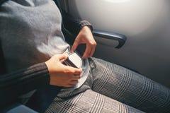 Женщина концепции безопасности азиатская прикрепляет ремень безопасности на самолете готовом для того чтобы принять  стоковое изображение rf